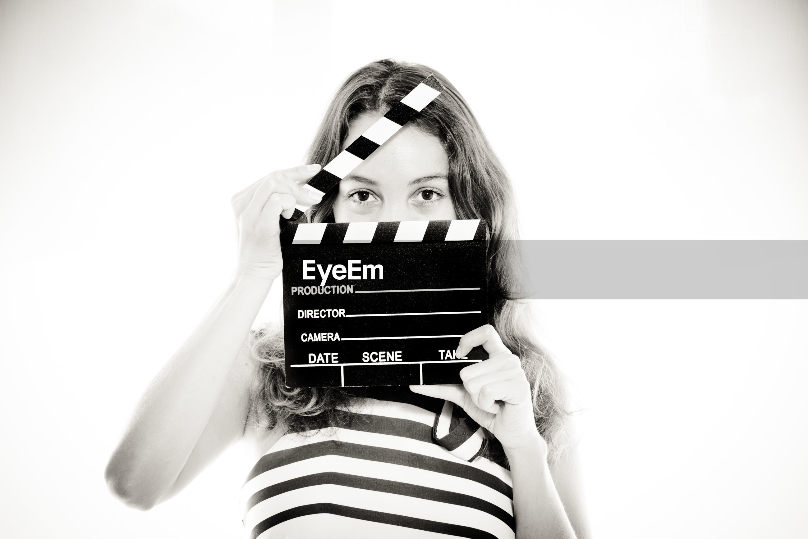 Portrait of young woman holding film slate over white background