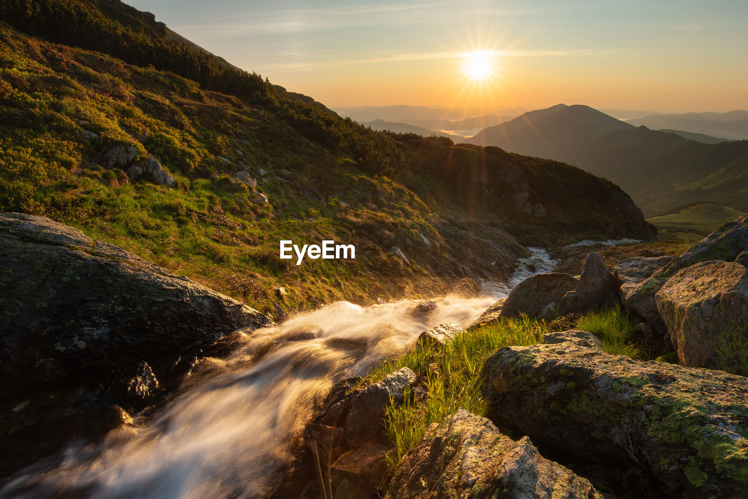 Scenic view of stream amidst rocks against sky during sunrise in rodnei mountains