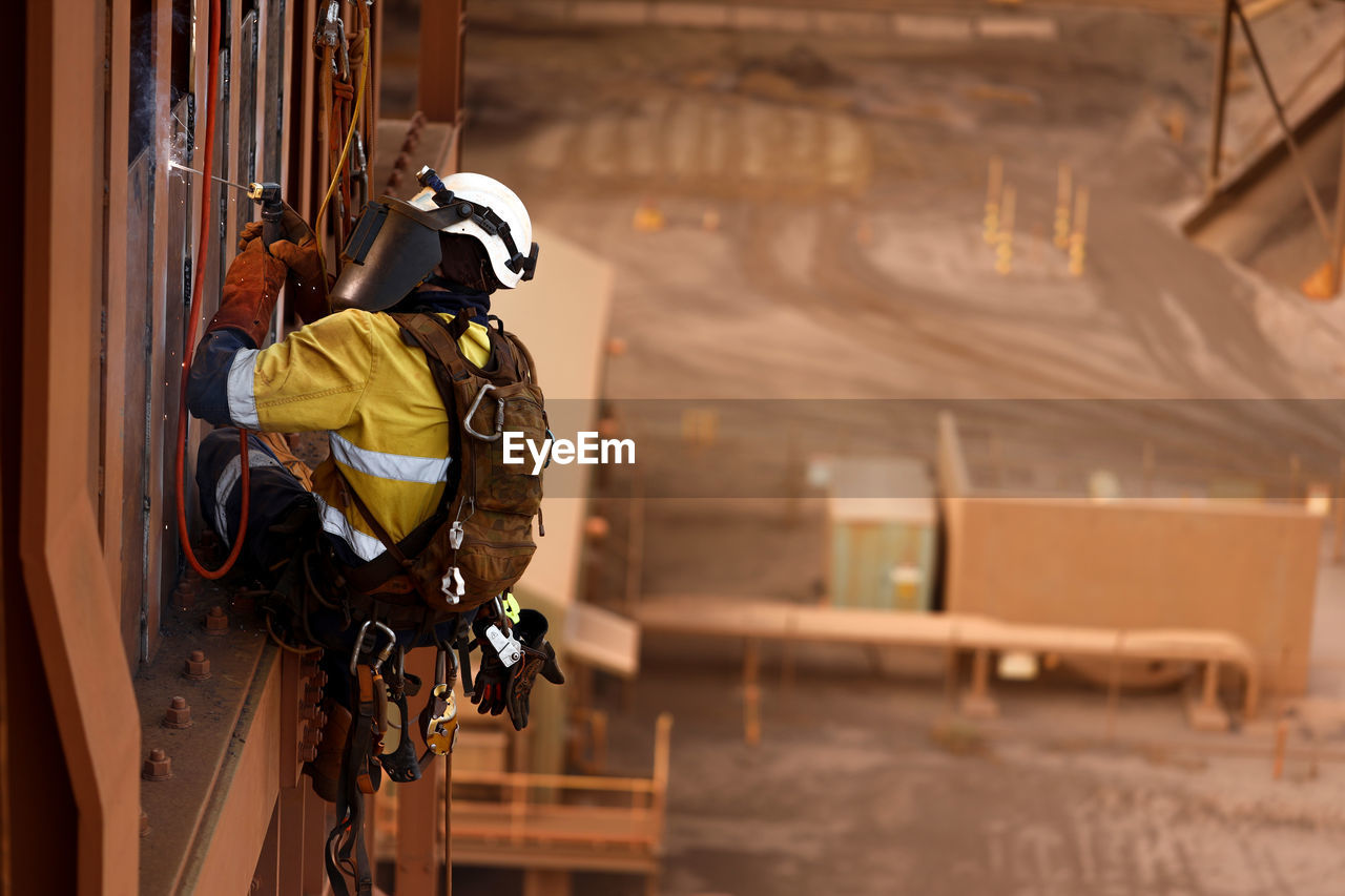 occupation, one person, real people, protection, safety, working, men, architecture, focus on foreground, security, built structure, hanging, day, outdoors, helmet, clothing, side view, protective workwear
