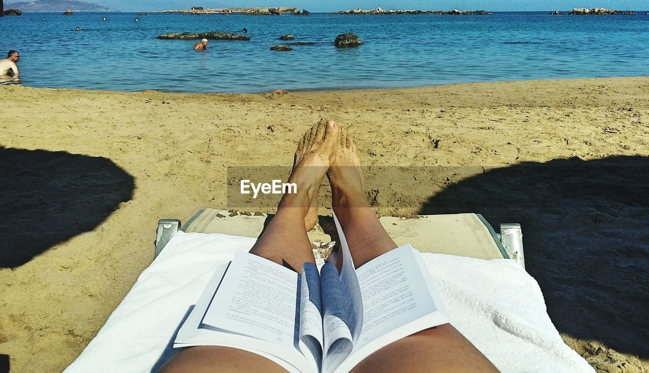 Open Book On Lap Of Woman Relaxing At Beach