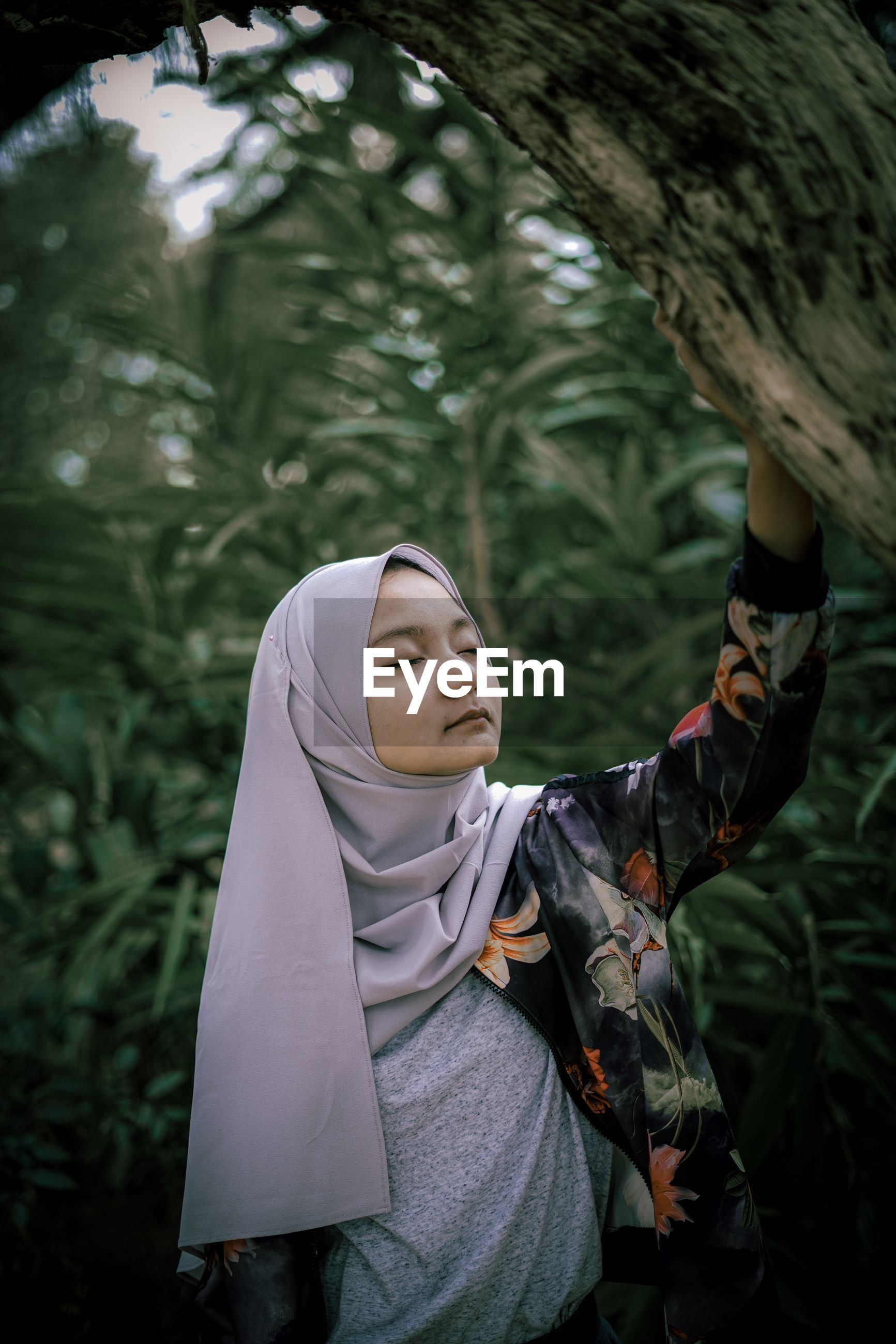Woman with eyes closed standing by tree
