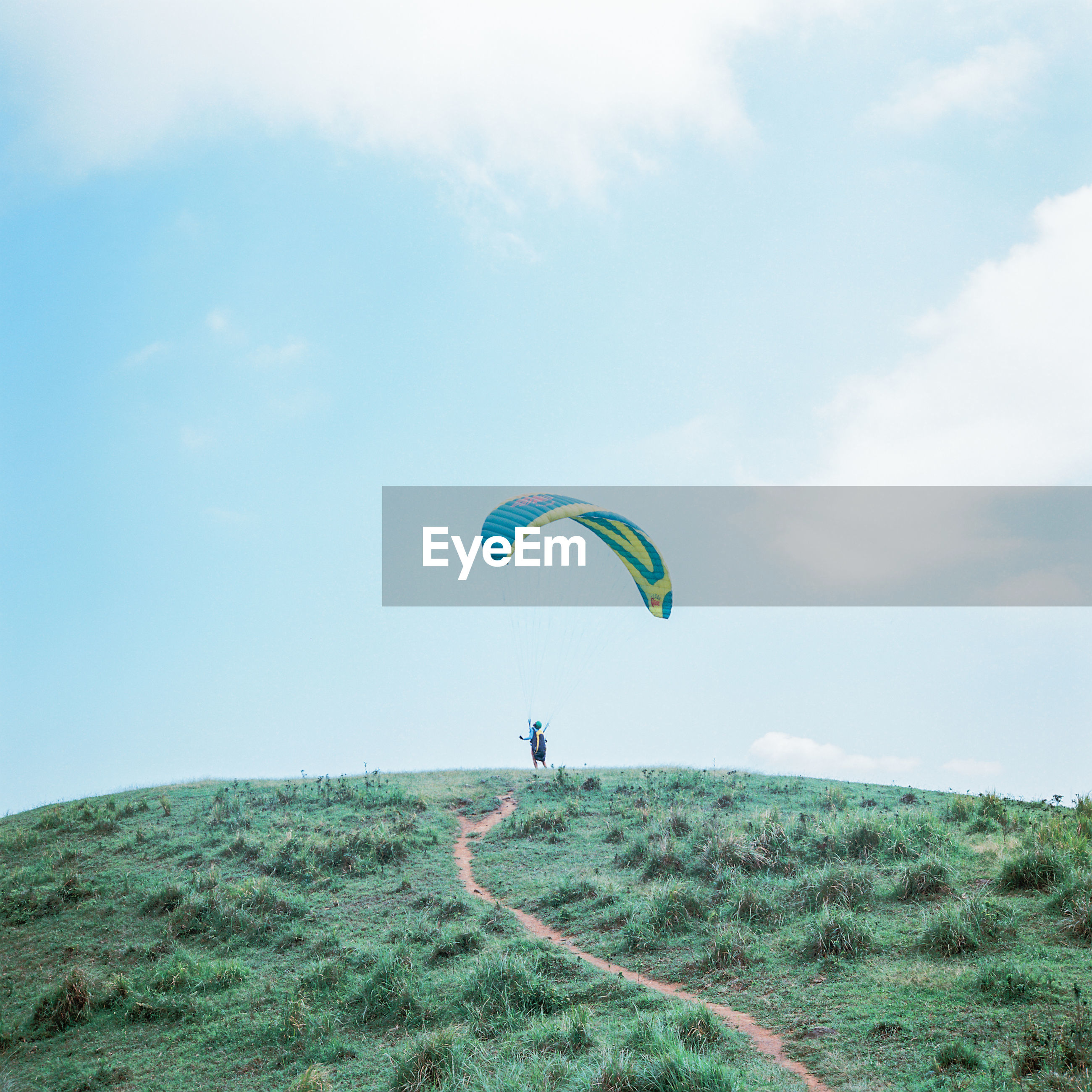 PEOPLE PARAGLIDING OVER GRASSY FIELD AGAINST SKY