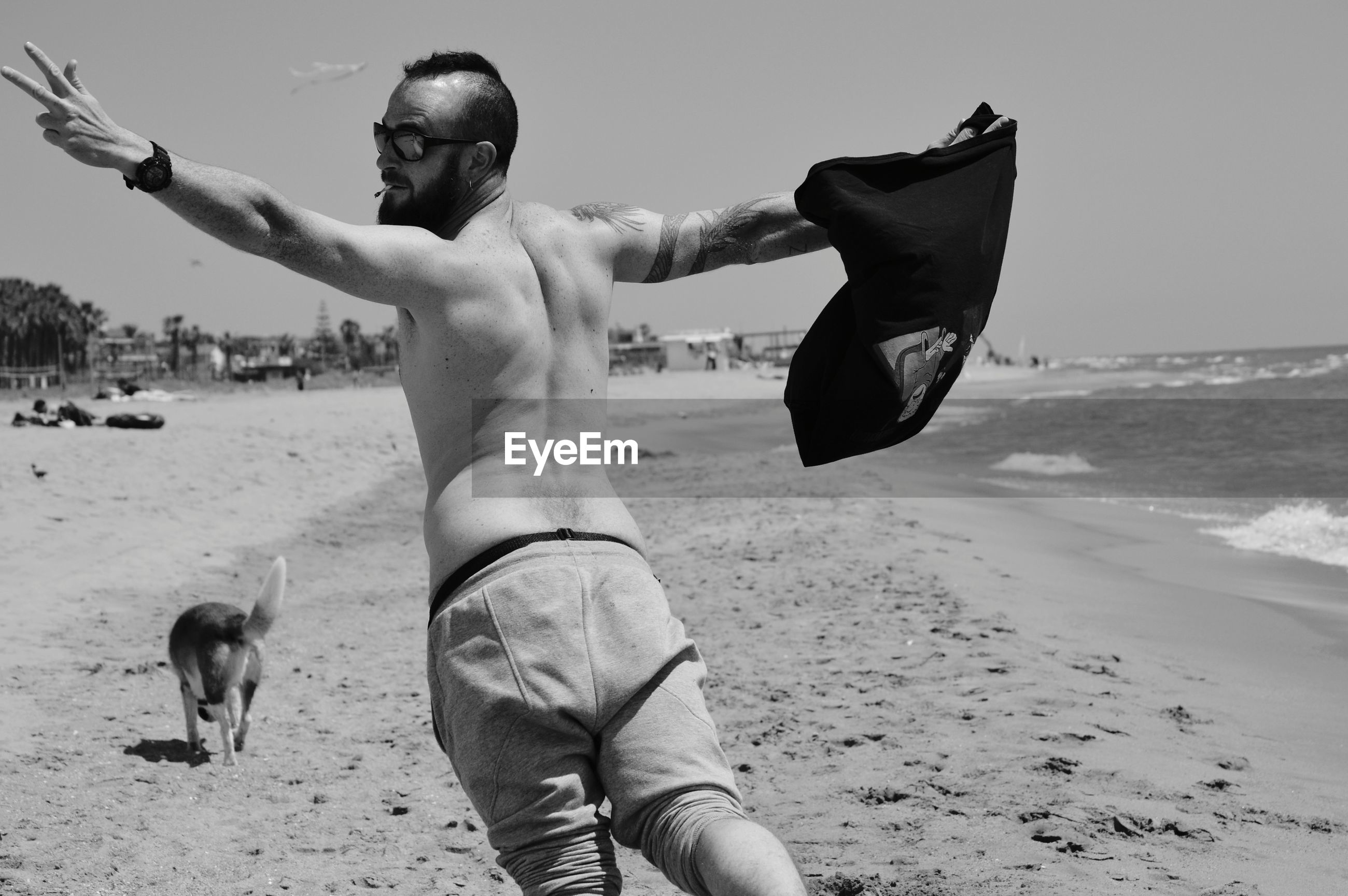 Rear view of shirtless man with arms outstretched standing on beach