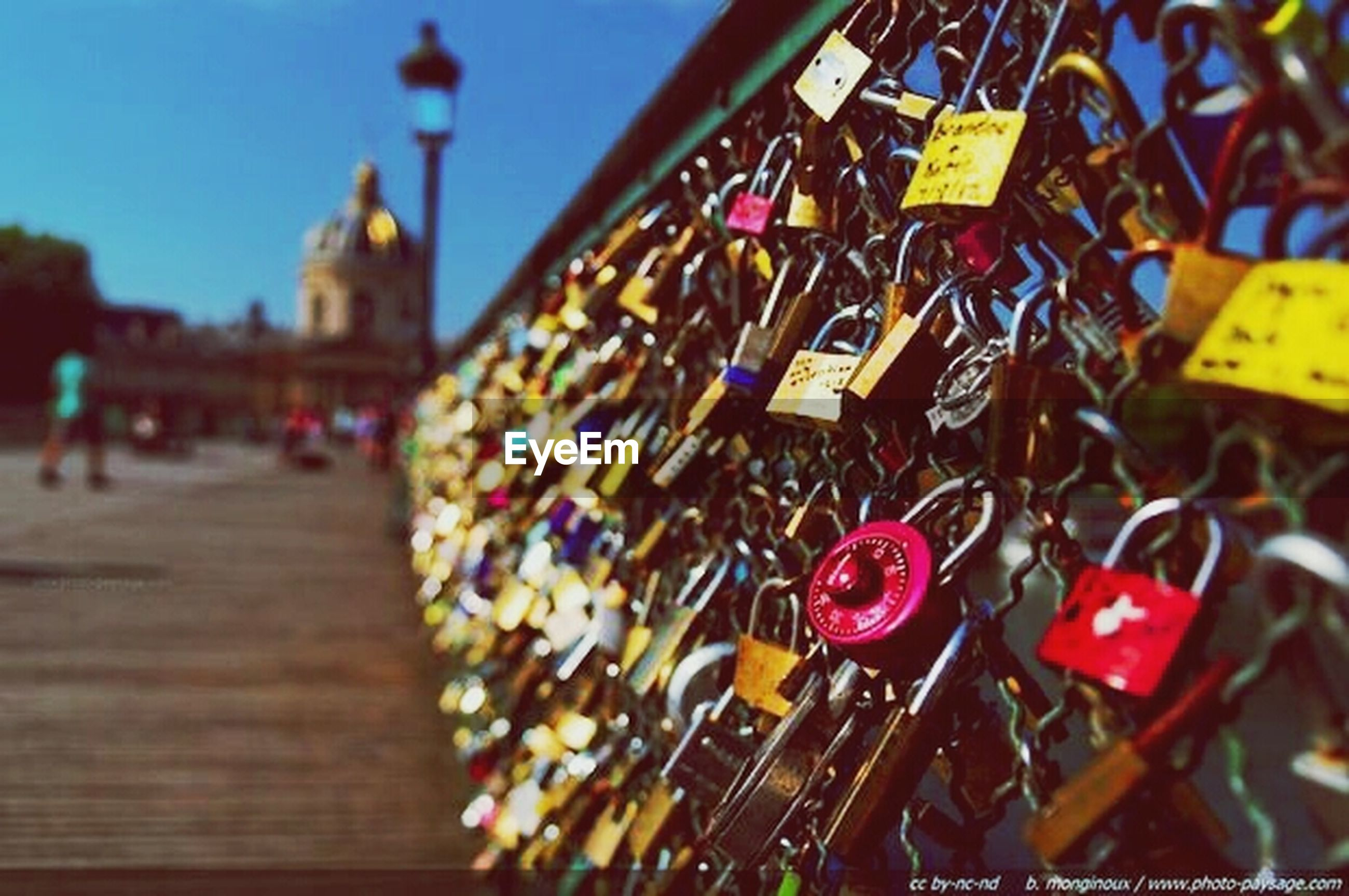 multi colored, built structure, architecture, building exterior, focus on foreground, padlock, outdoors, incidental people, selective focus, metal, wood - material, hanging, day, in a row, large group of objects, decoration, variation, cultures, city, railing