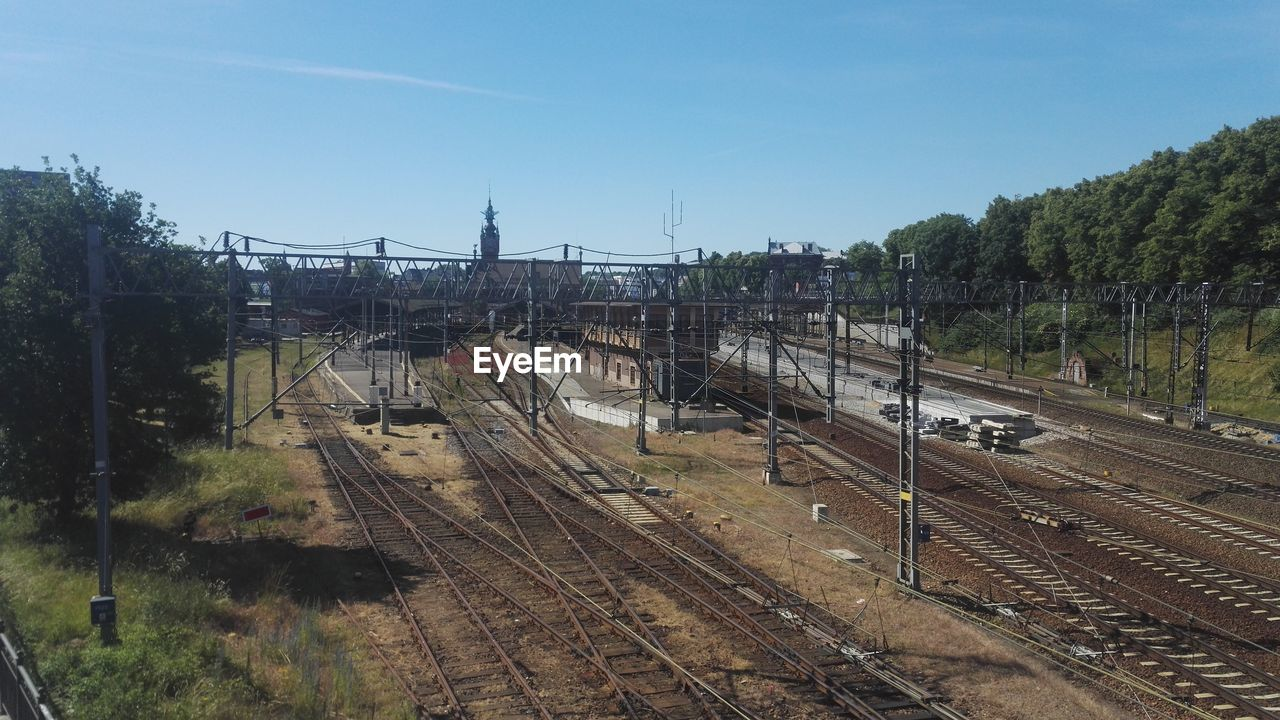 rail transportation, track, railroad track, transportation, tree, mode of transportation, plant, train, public transportation, sky, built structure, train - vehicle, nature, architecture, no people, day, high angle view, outdoors, connection, travel, shunting yard, power supply