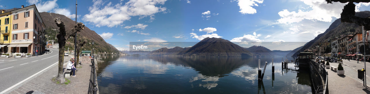 water, sky, cloud - sky, mountain, architecture, reflection, built structure, building exterior, nature, city, transportation, day, building, beauty in nature, panoramic, scenics - nature, mode of transportation, incidental people, residential district