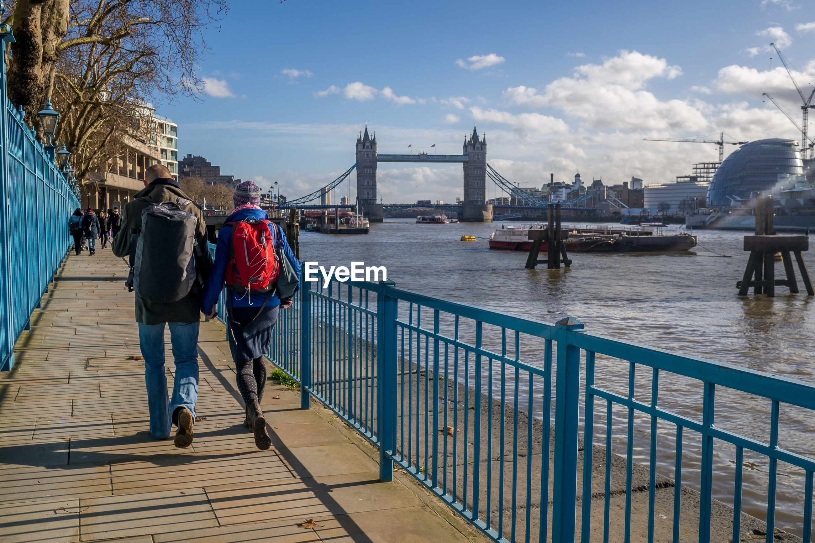 Rear view of people walking on footpath by tower bridge over thames river against sky