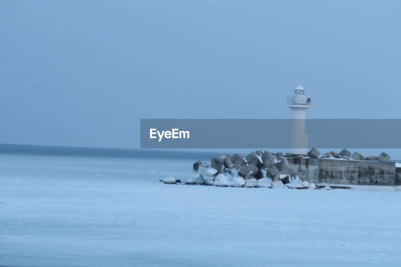 water, sky, sea, built structure, lighthouse, scenics - nature, tower, architecture, cold temperature, guidance, horizon over water, horizon, nature, building exterior, copy space, building, winter, clear sky, land, no people, outdoors