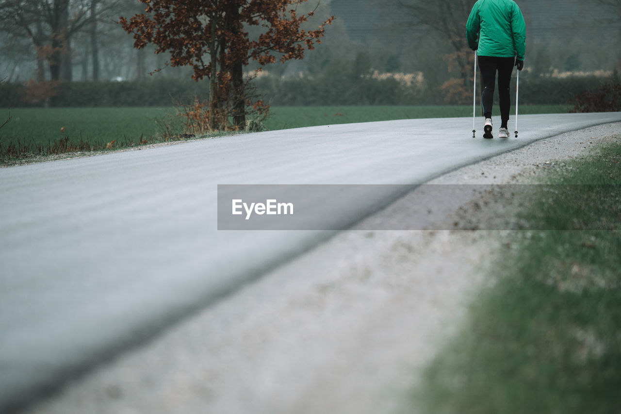 Low Section Of Man Walking On Road During Foggy Weather