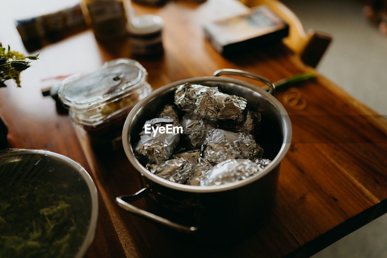 High angle view of baked potatoes in foil on table