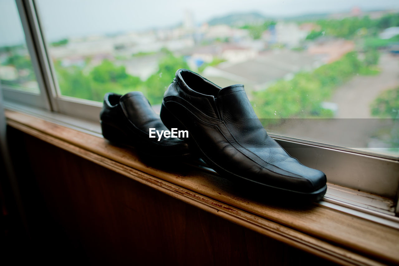 shoe, pair, no people, indoors, day, absence, close-up, black color, still life, focus on foreground, window, selective focus, glass - material, compatibility, fashion, wood - material, boot, transparent, clothing, personal accessory, leather, menswear
