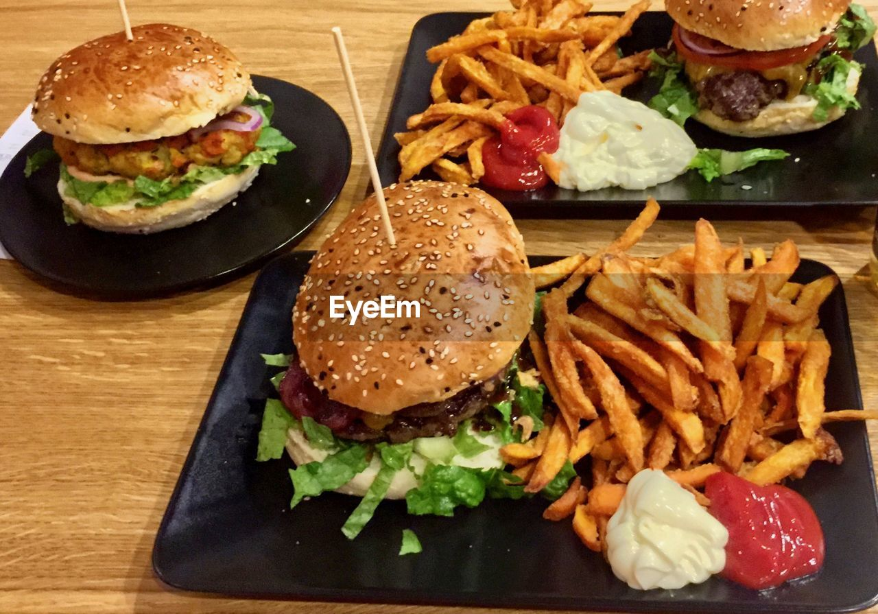 hamburger, food and drink, food, french fries, burger, ready-to-eat, indoors, lettuce, fast food, freshness, serving size, tomato, unhealthy eating, table, bun, no people, vegetable, prepared potato, close-up, meat, take out food, salad, indulgence, plate, beef, deep fried, dip, day
