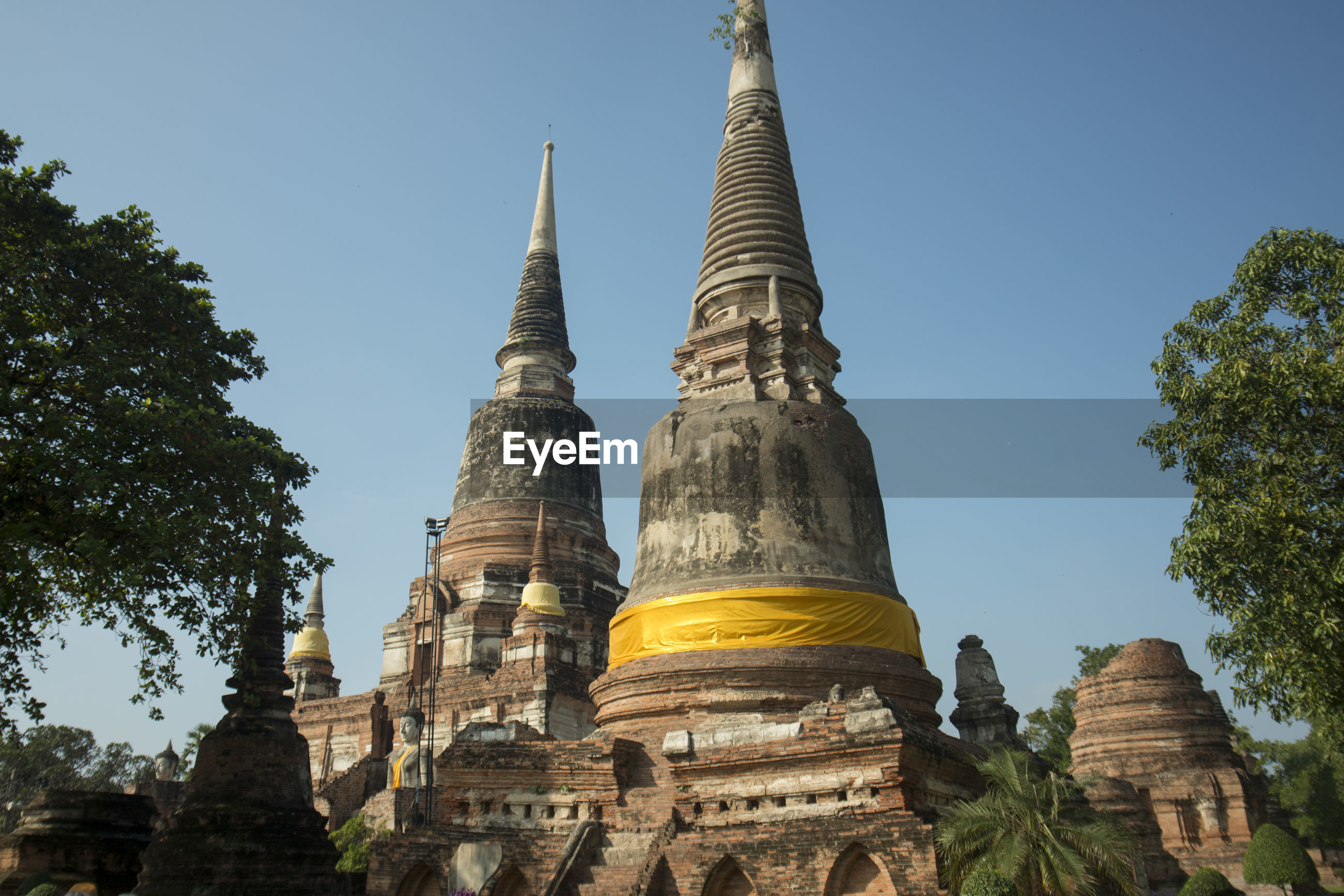 Low angle view of buddhist temple against clear blue sky