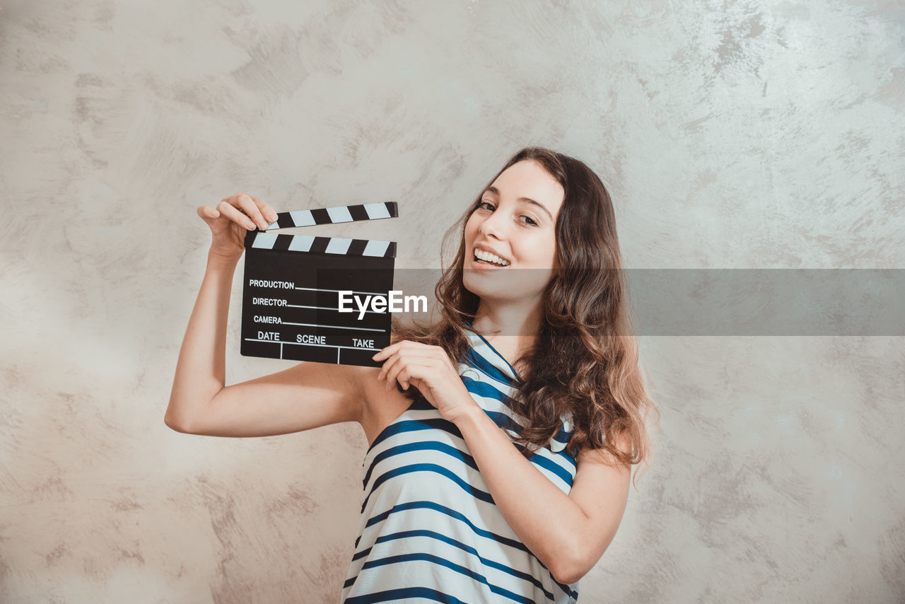 Portrait of cheerful young woman holding film slate by wall