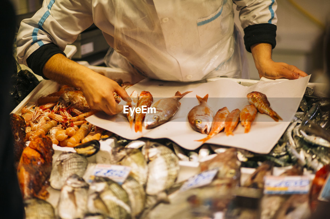 Midsection Of Man Selling Fish At Market Stall