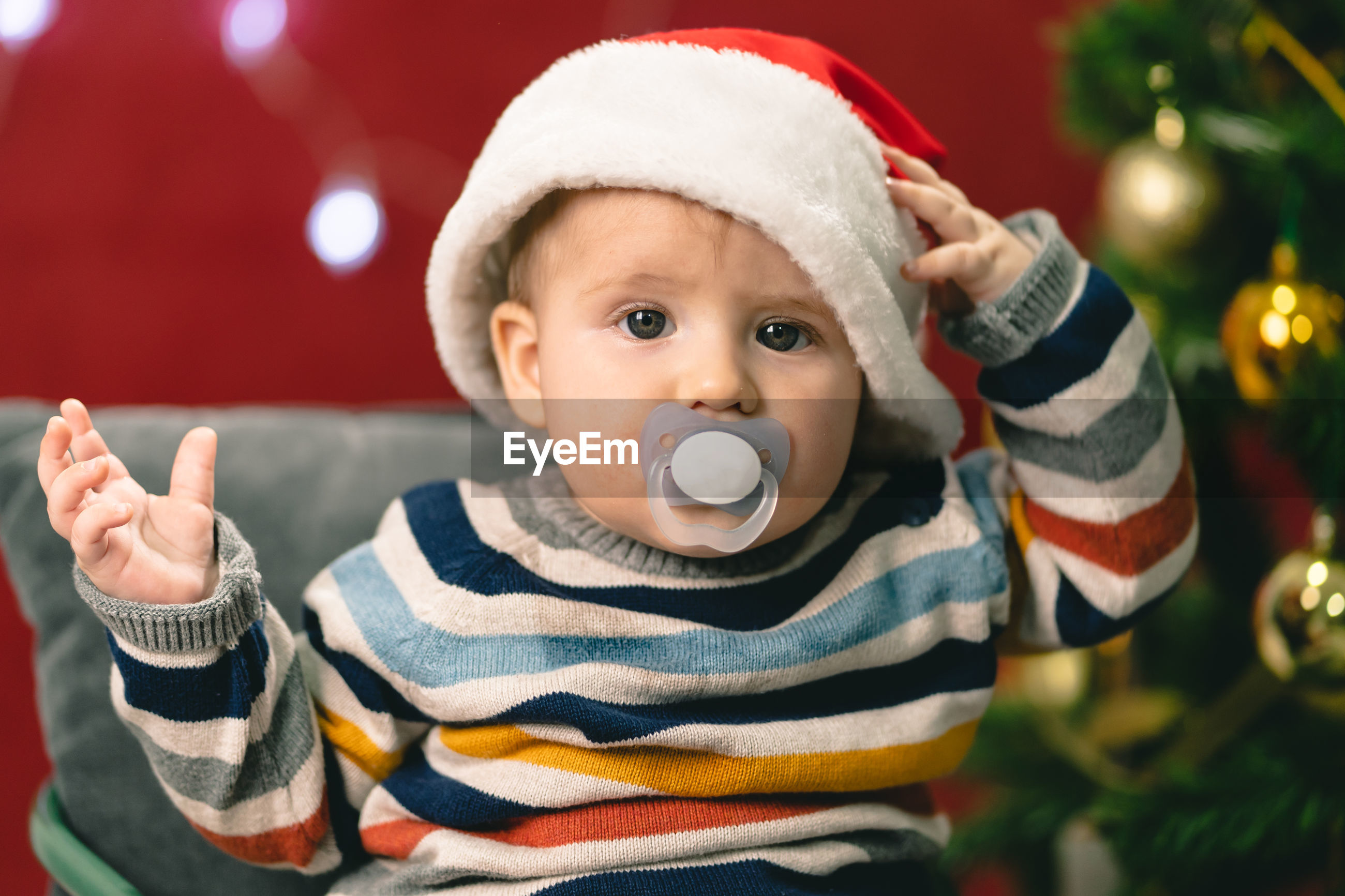 Portrait of cute baby boy with pacifier in mouth wearing santa hat