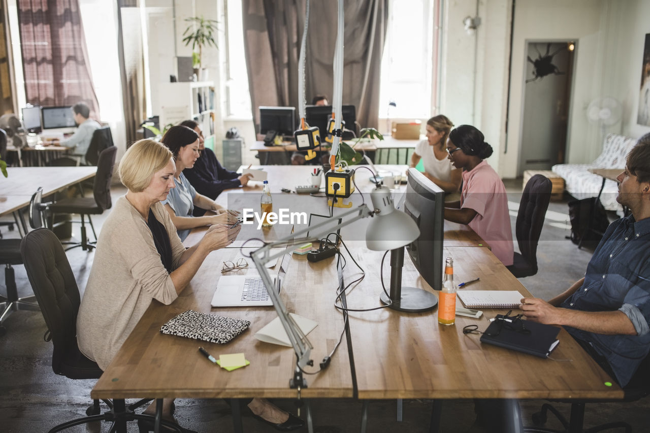 group of people, real people, women, table, technology, working, sitting, computer, indoors, adult, laptop, wireless technology, using laptop, business, casual clothing, teamwork, cooperation, creativity, communication, colleague, coworker, new business
