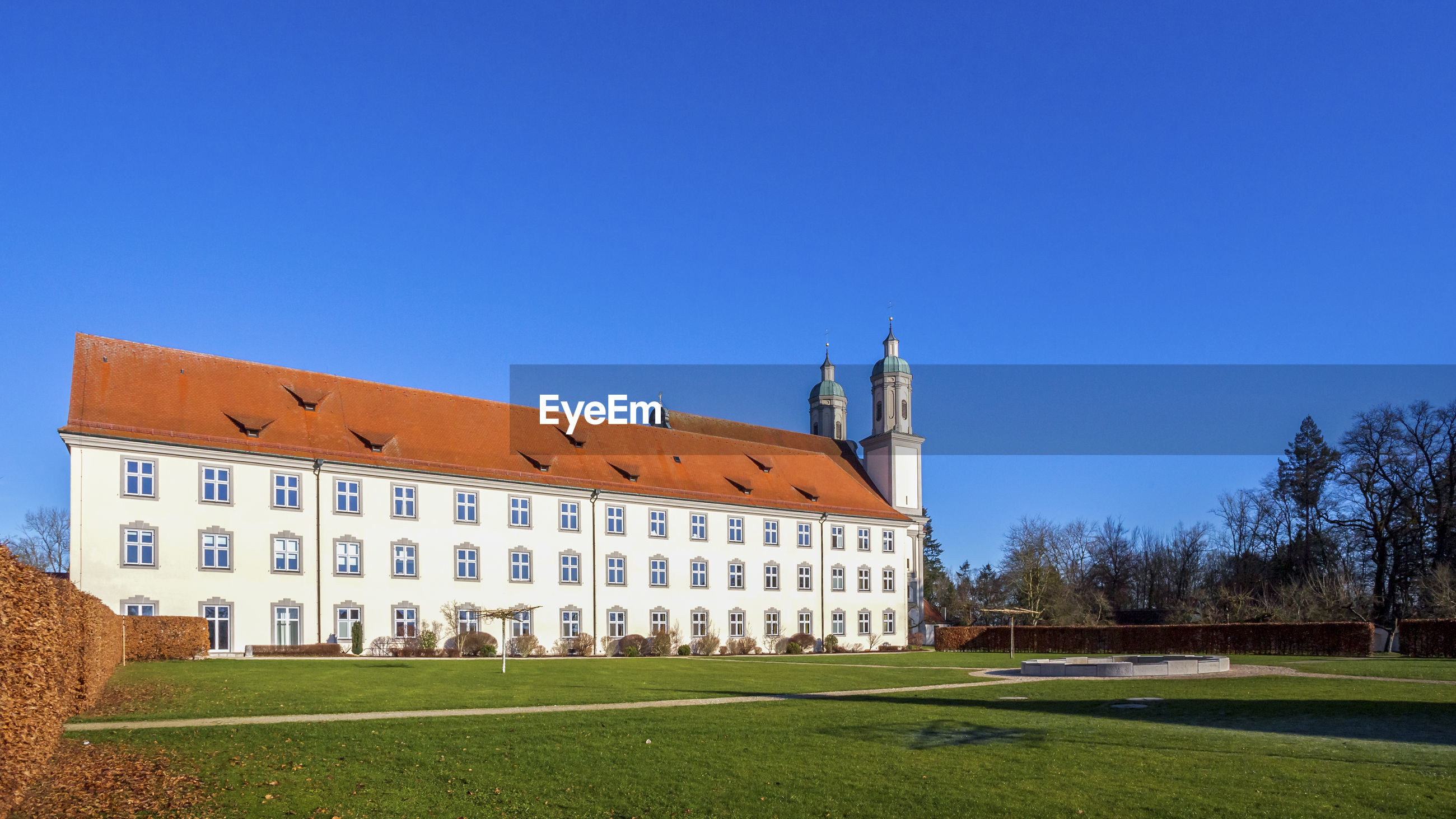 Holzen abbey and lawn against clear blue sky