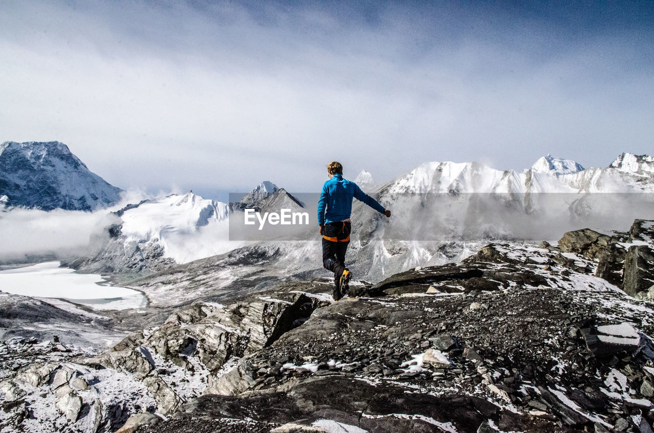 Full Length Rear View Of Man Walking On Landscape By Snowcapped Mountains Against Sky