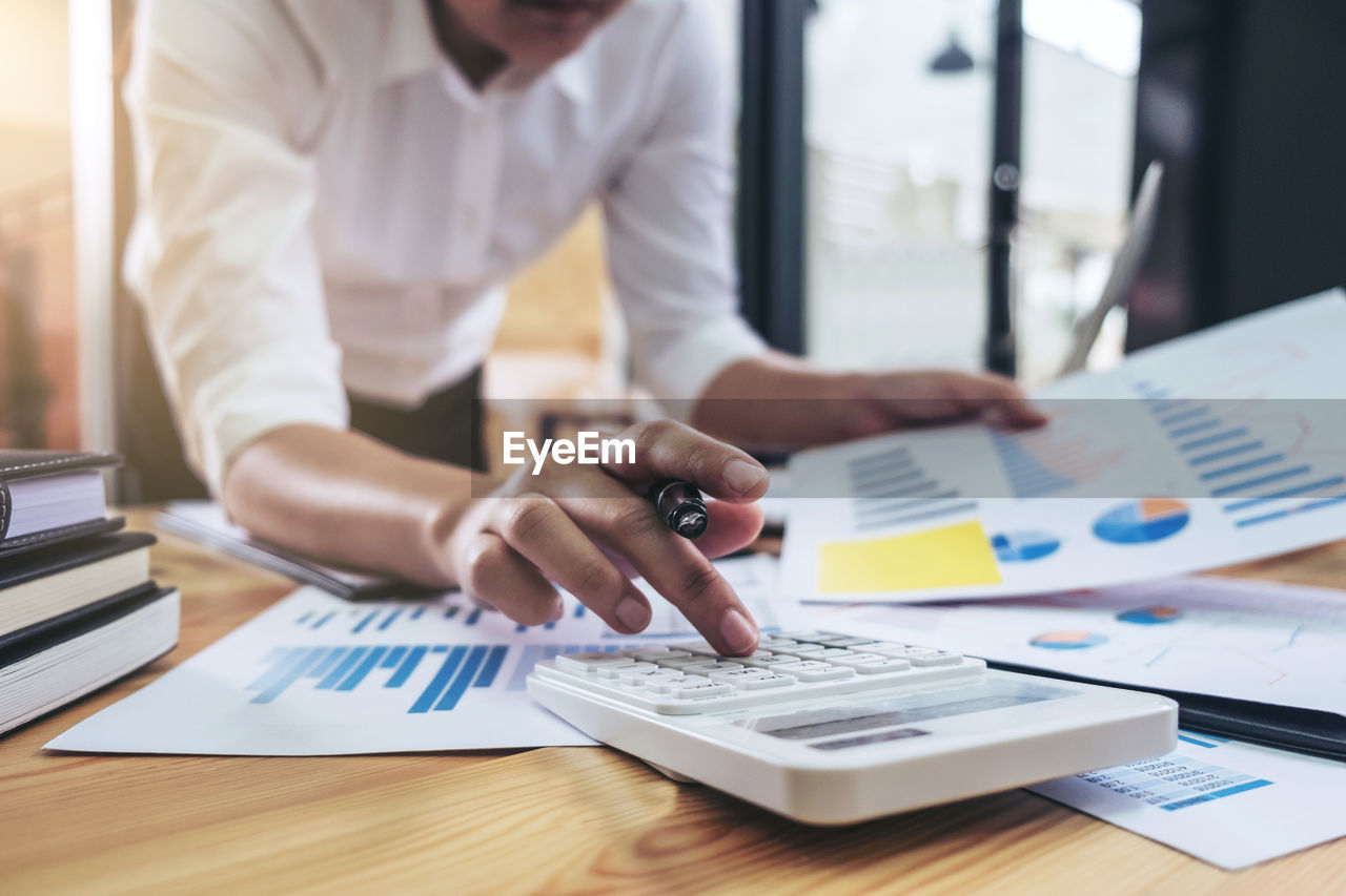 Midsection Of Businessman Using Calculator At Desk