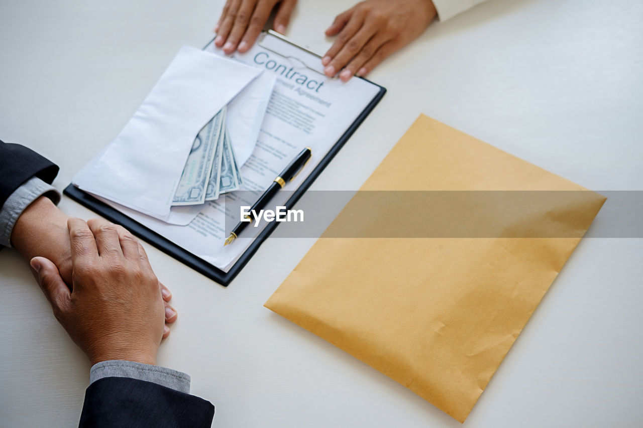 Cropped Hands Of Business People With Paper Currency And Documents At Table