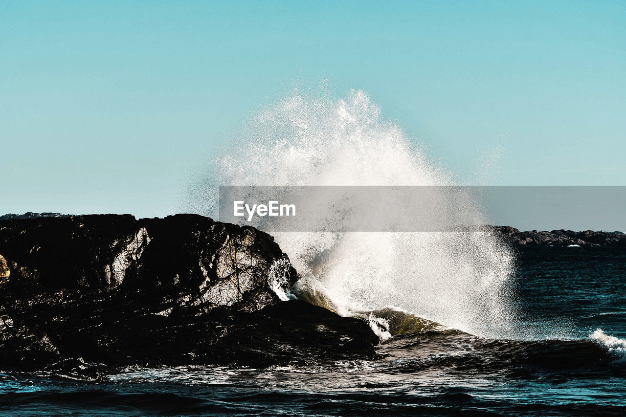 water, motion, sea, power in nature, power, wave, crash, beauty in nature, rock, hitting, force, breaking, no people, nature, clear sky, splashing, sky, rock - object, day, outdoors