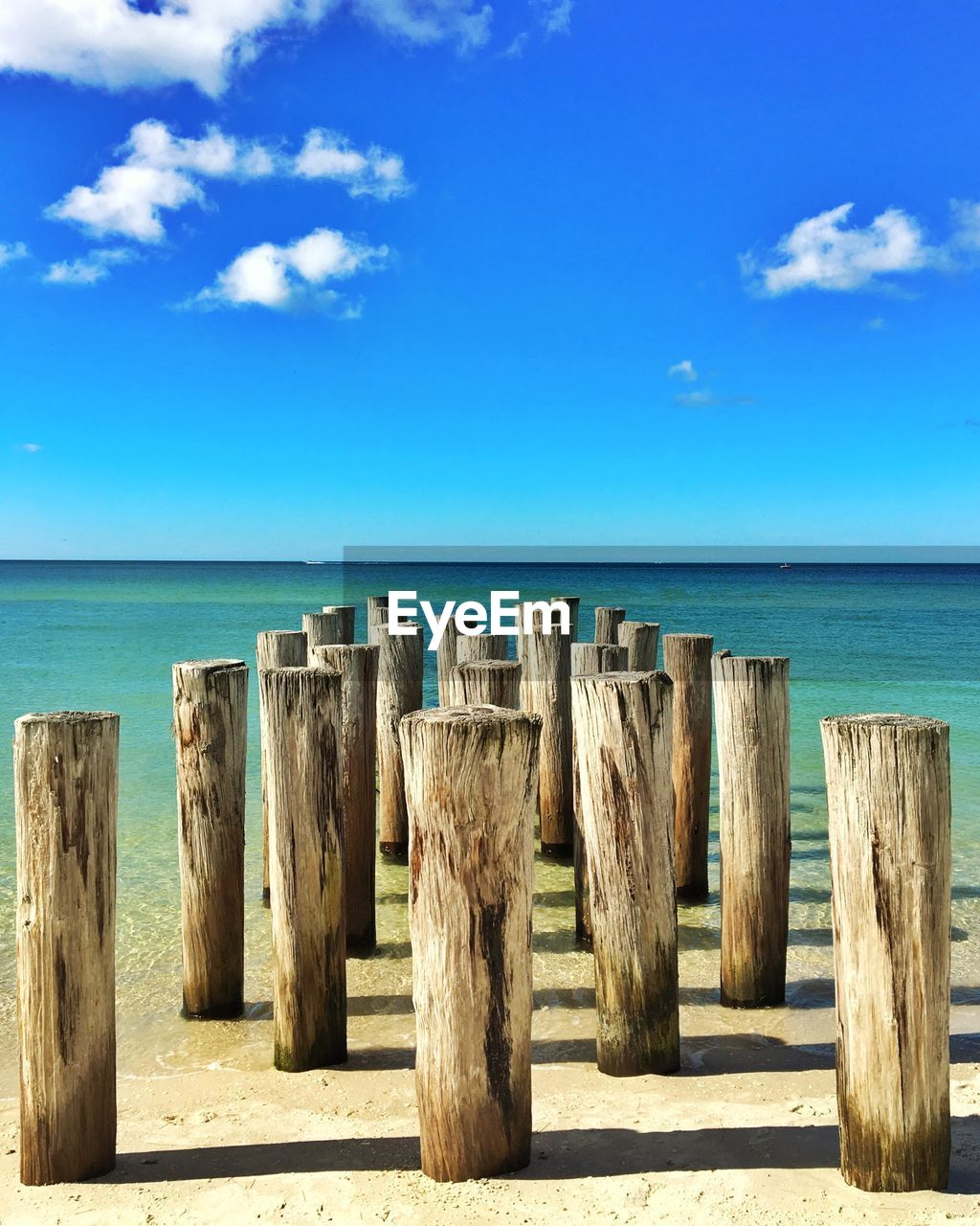 Close-Up Of Wooden Poles In Calm Blue Water