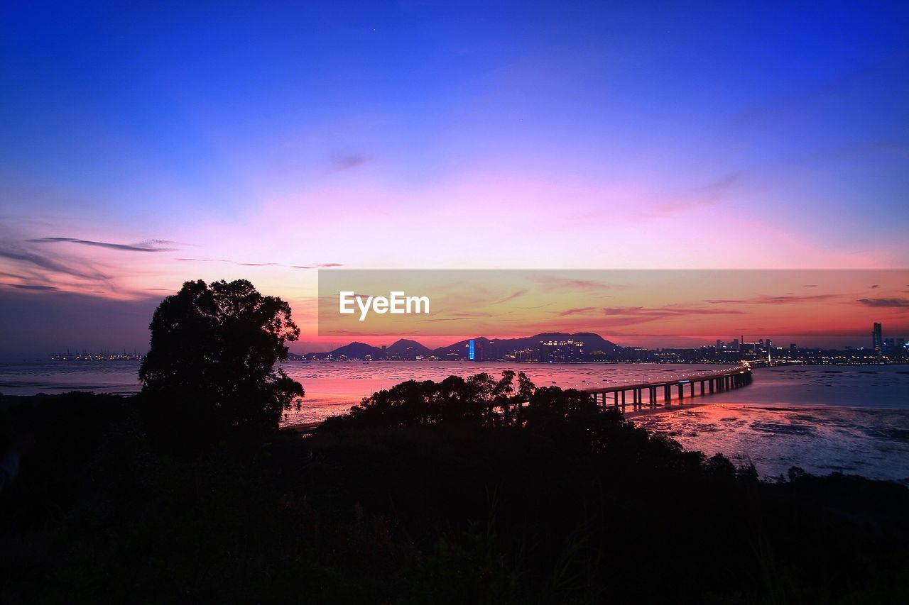 SCENIC VIEW OF BAY AGAINST SKY DURING SUNSET