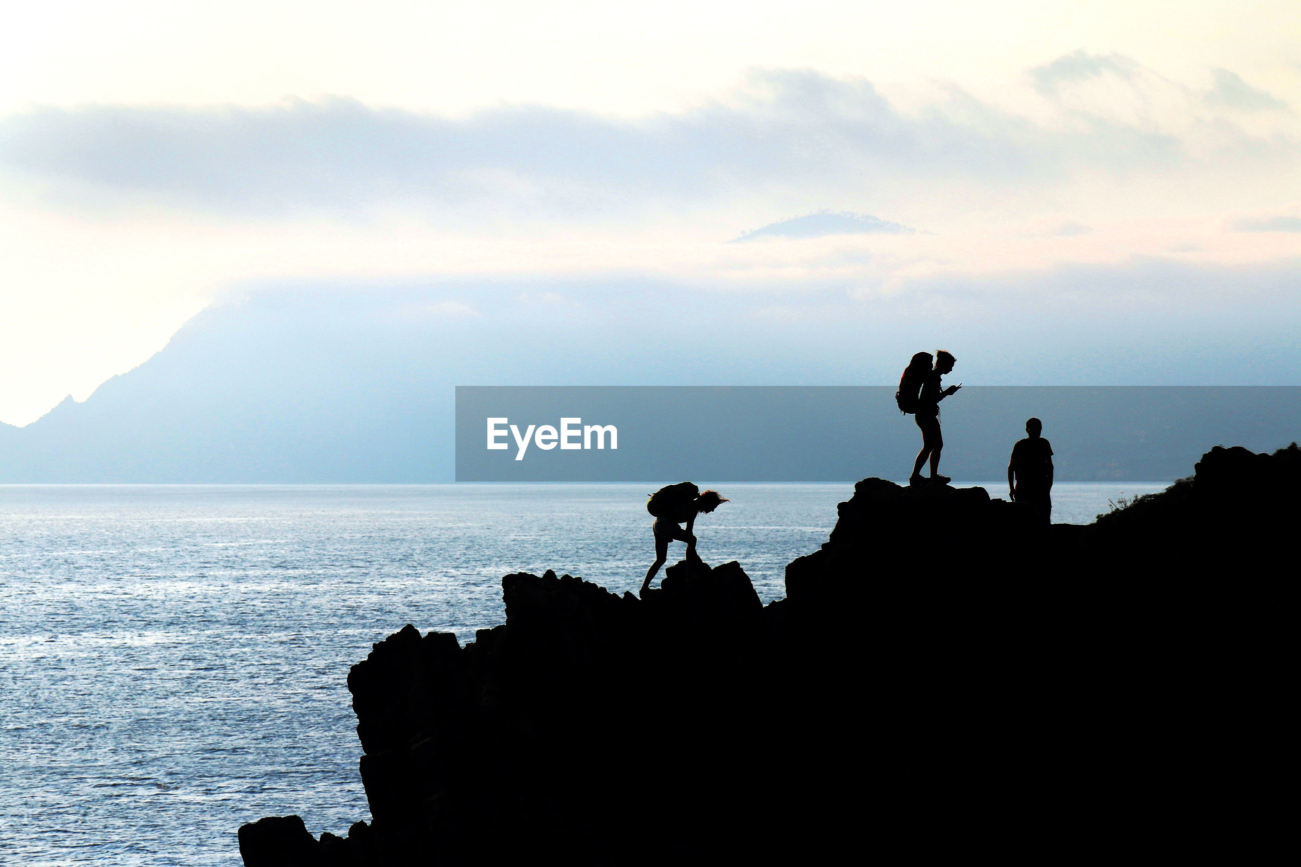 Silhouette hikers standing on mountain by sea against cloudy sky