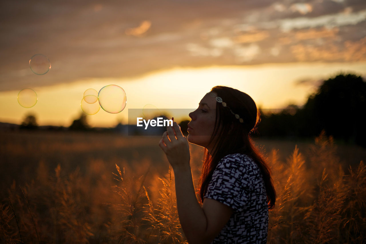 Young Woman Blowing Bubbles On Wheat Field Against Cloudy Sky During Sunset