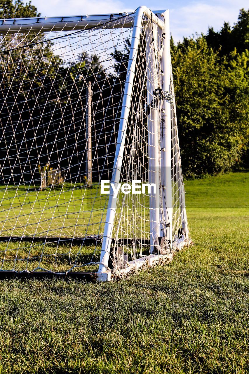 grass, sport, field, day, outdoors, no people, playing field, net - sports equipment, tree, goal post, soccer field, sky, nature