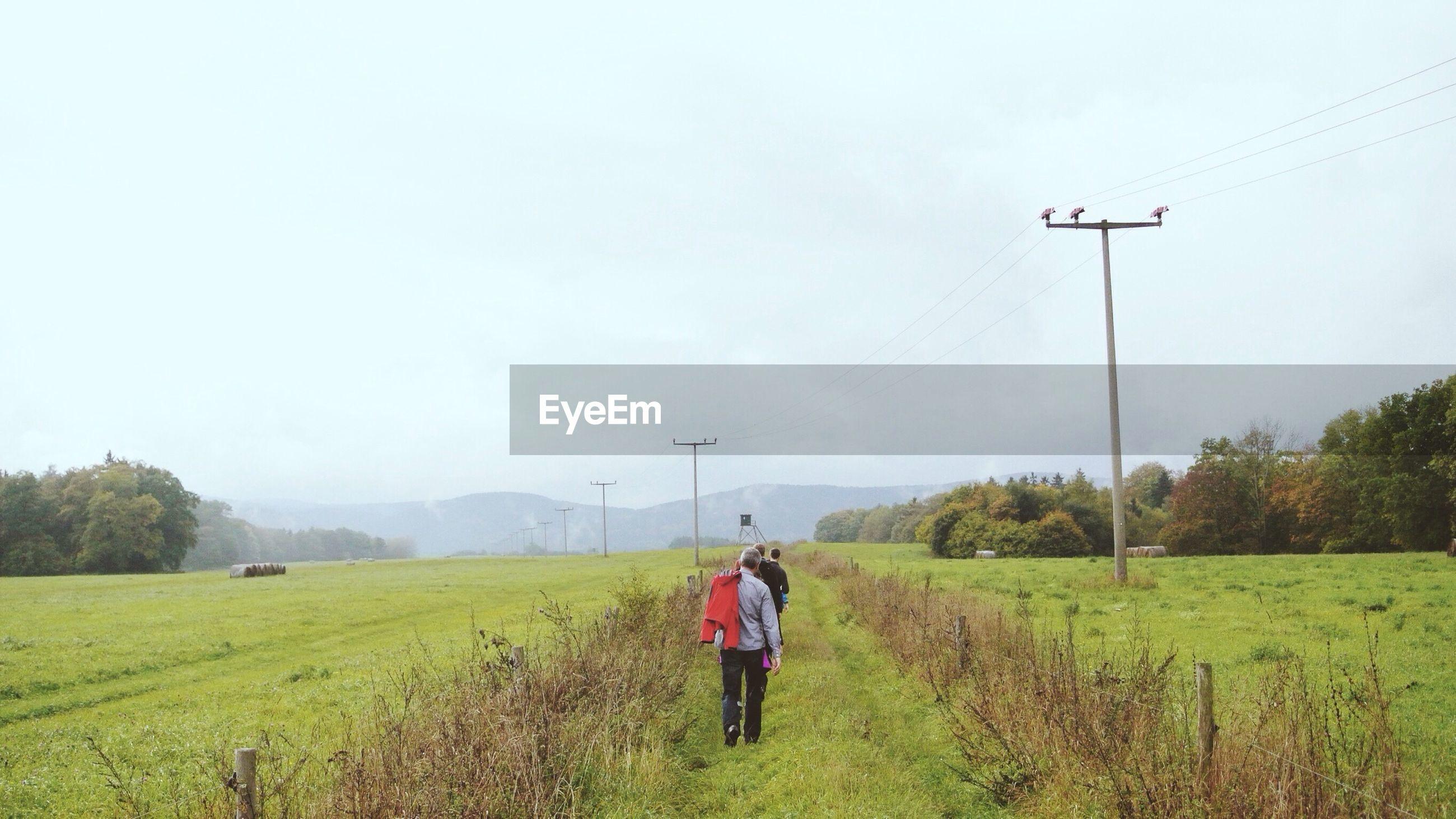 Rear view of people walking on grassy field against sky