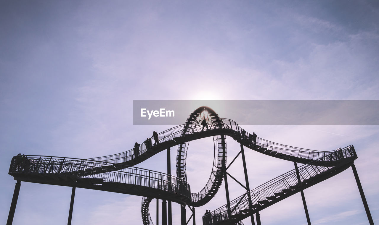 Low angle view of silhouette people on tiger and turtle magic mountain against sky