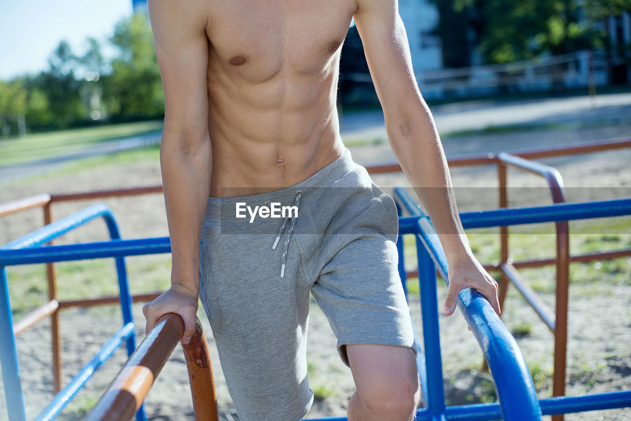 one person, real people, leisure activity, lifestyles, shirtless, focus on foreground, men, midsection, day, casual clothing, standing, railing, playground, park - man made space, park, males, front view, nature, outdoor play equipment, shorts