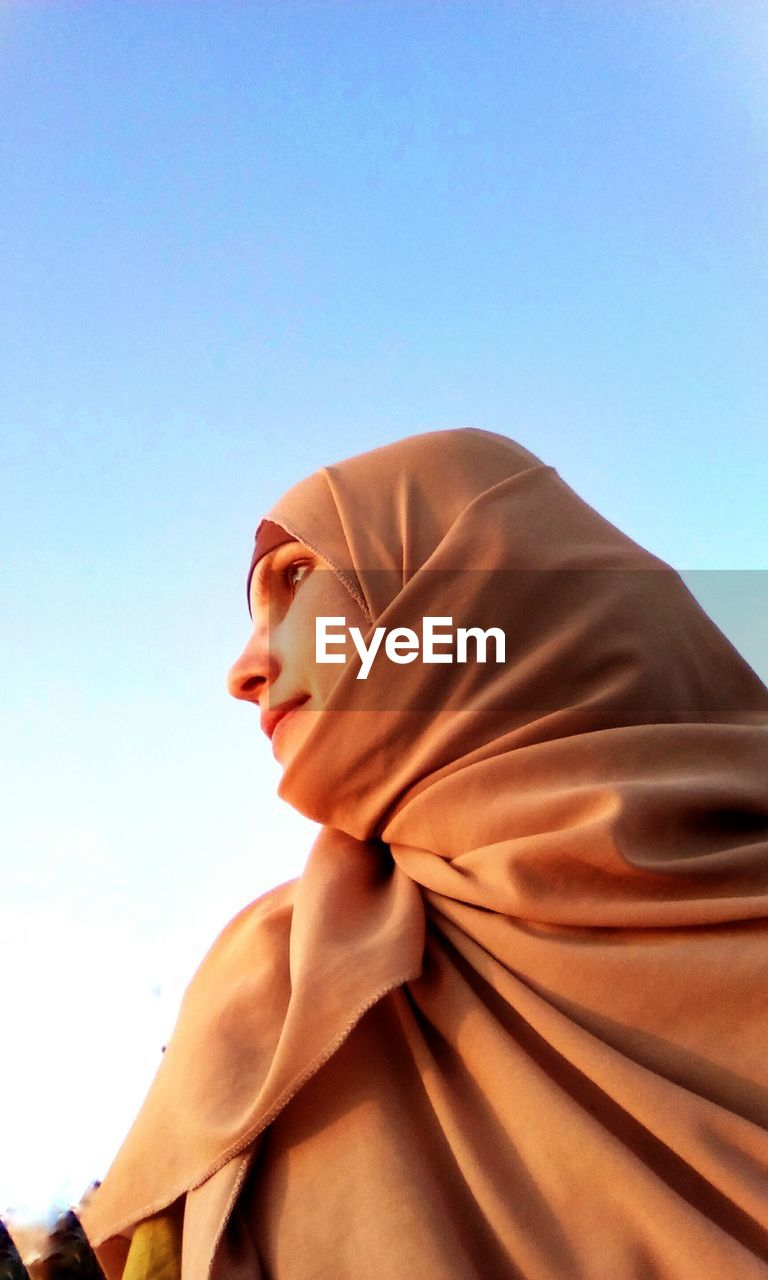 Low Angle View Of Woman Against Clear Sky
