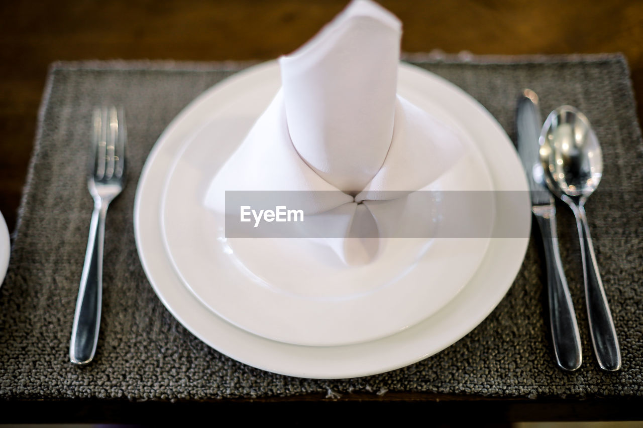 HIGH ANGLE VIEW OF EMPTY PLATE WITH COFFEE ON TABLE