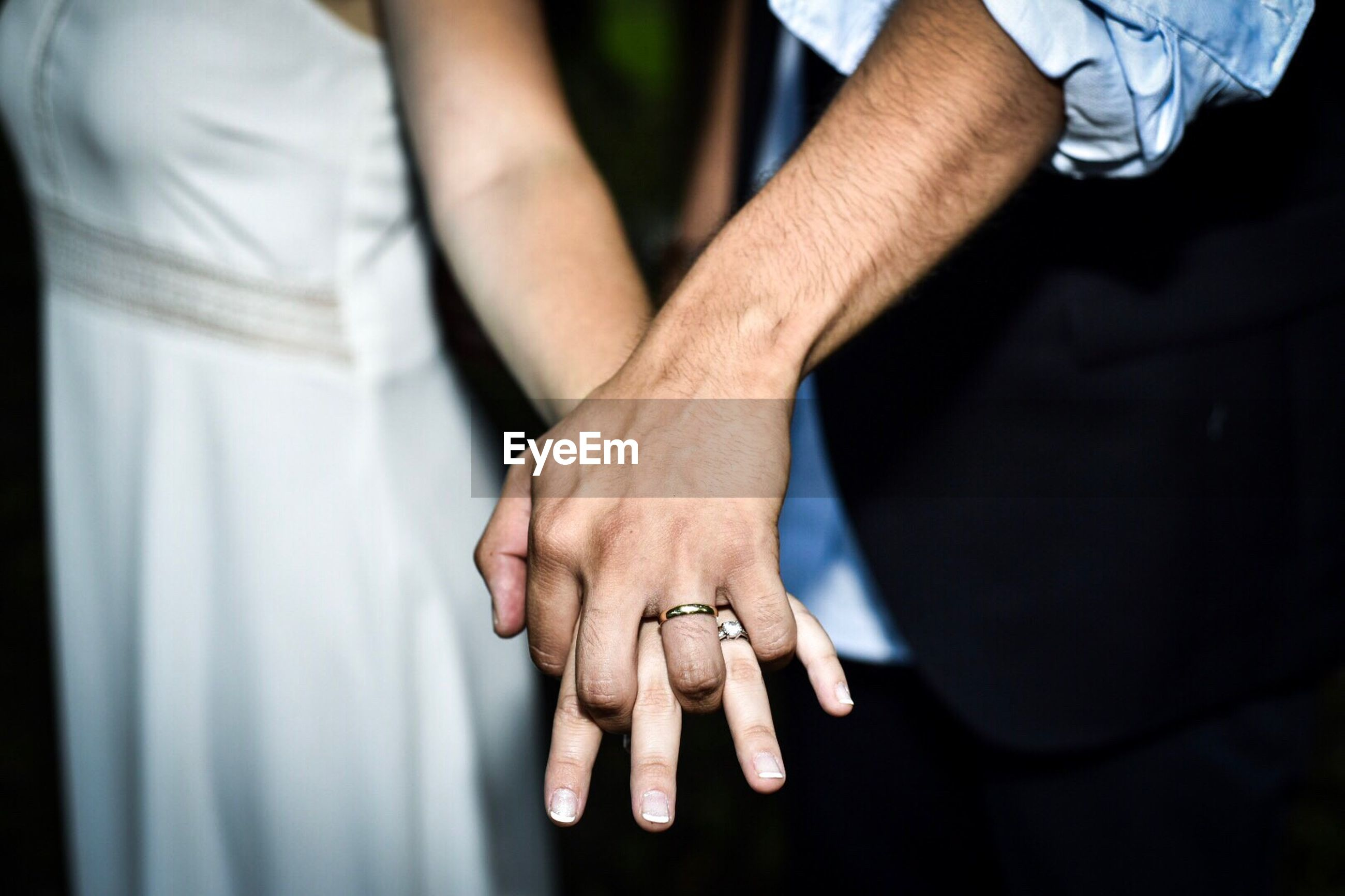 Close-up of couple wearing rings while holding hands