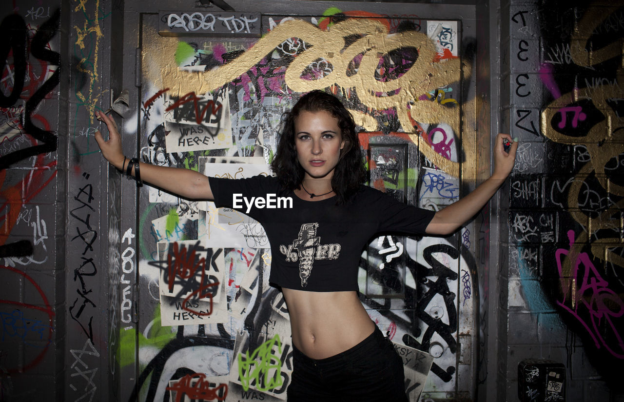 PORTRAIT OF YOUNG WOMAN STANDING AGAINST GRAFFITI