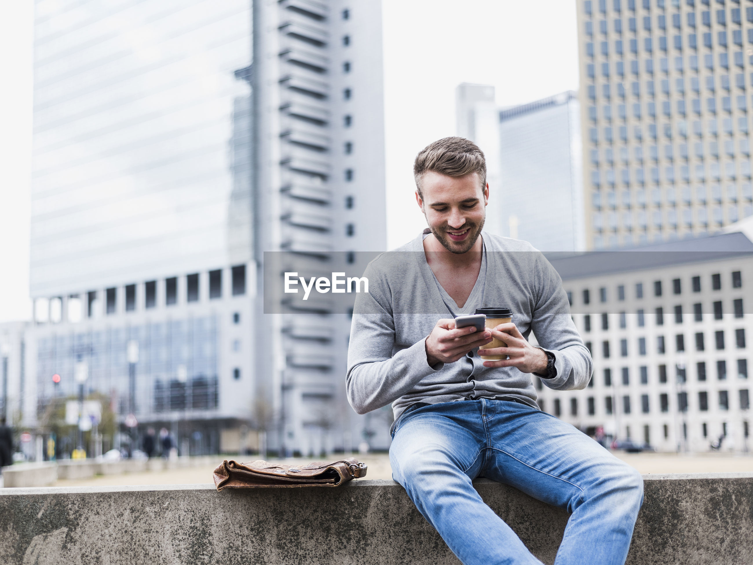 YOUNG MAN USING SMART PHONE WHILE SITTING ON CITY