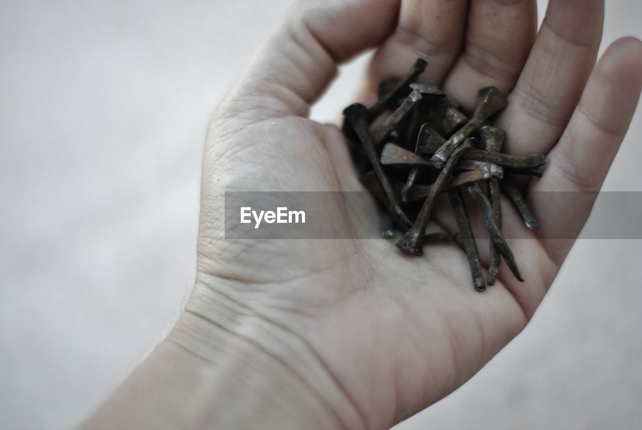 CLOSE-UP OF HUMAN HAND HOLDING RING