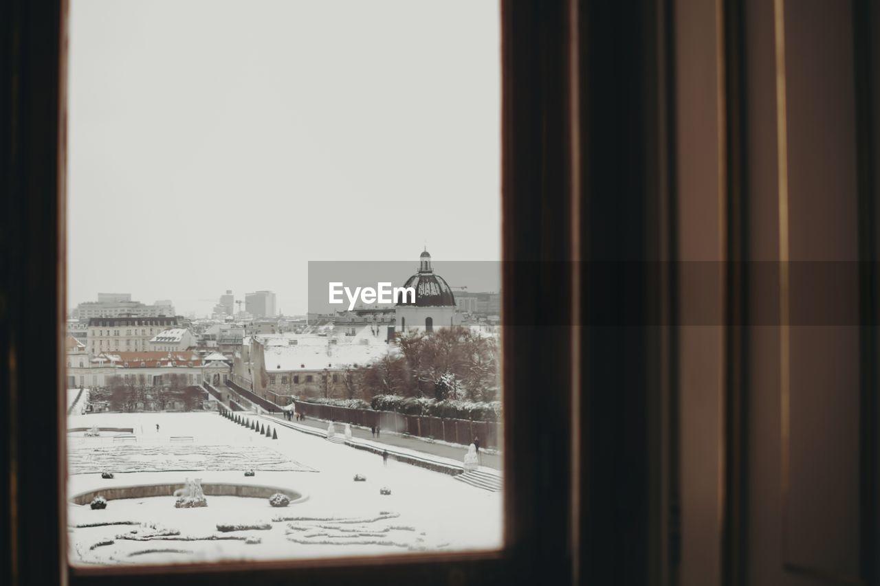 Snow Covered City Against Clear Sky Seen Through Window