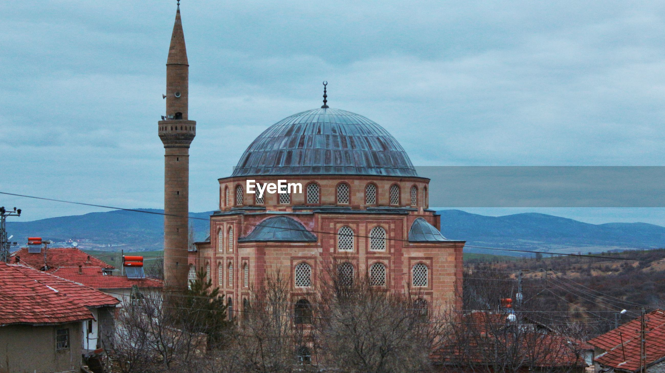 Mosque in city against sky