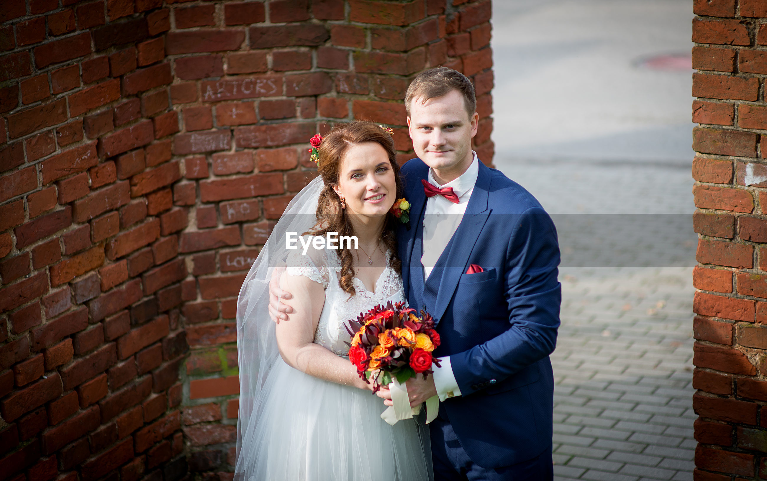 Bride and groom standing by brick wall