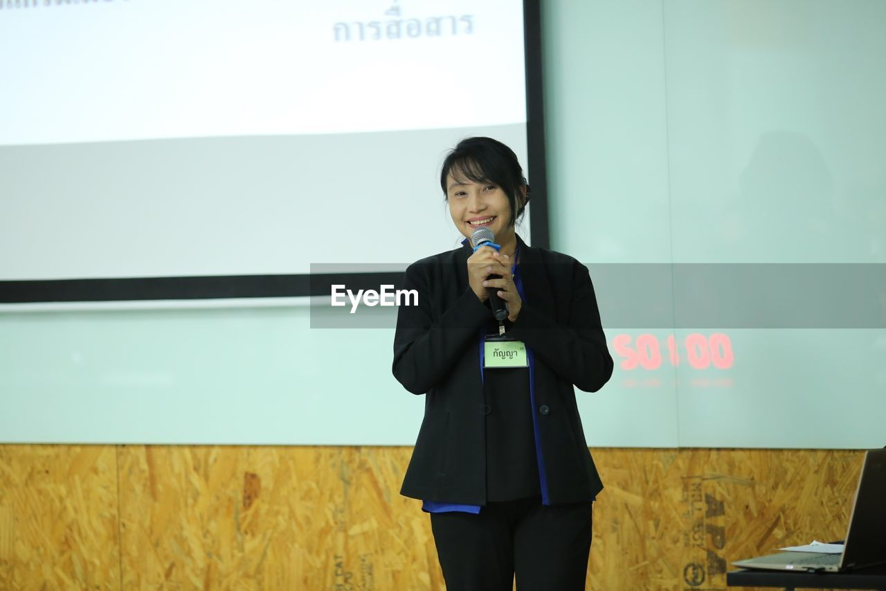 Portrait Of Smiling Businesswoman Holding Microphone While Standing Against Projection Screen