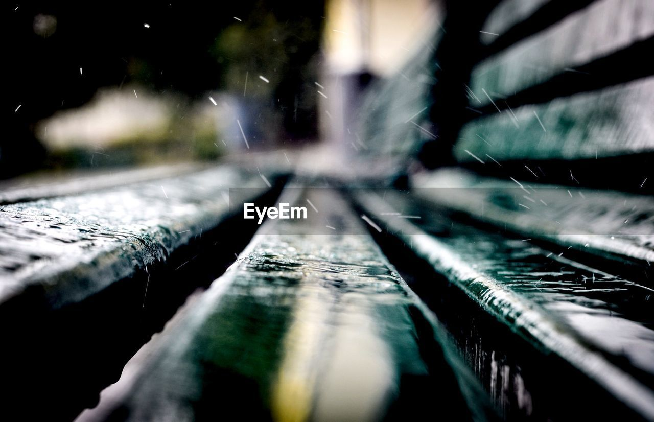 Close-up of raindrops on wooden bench