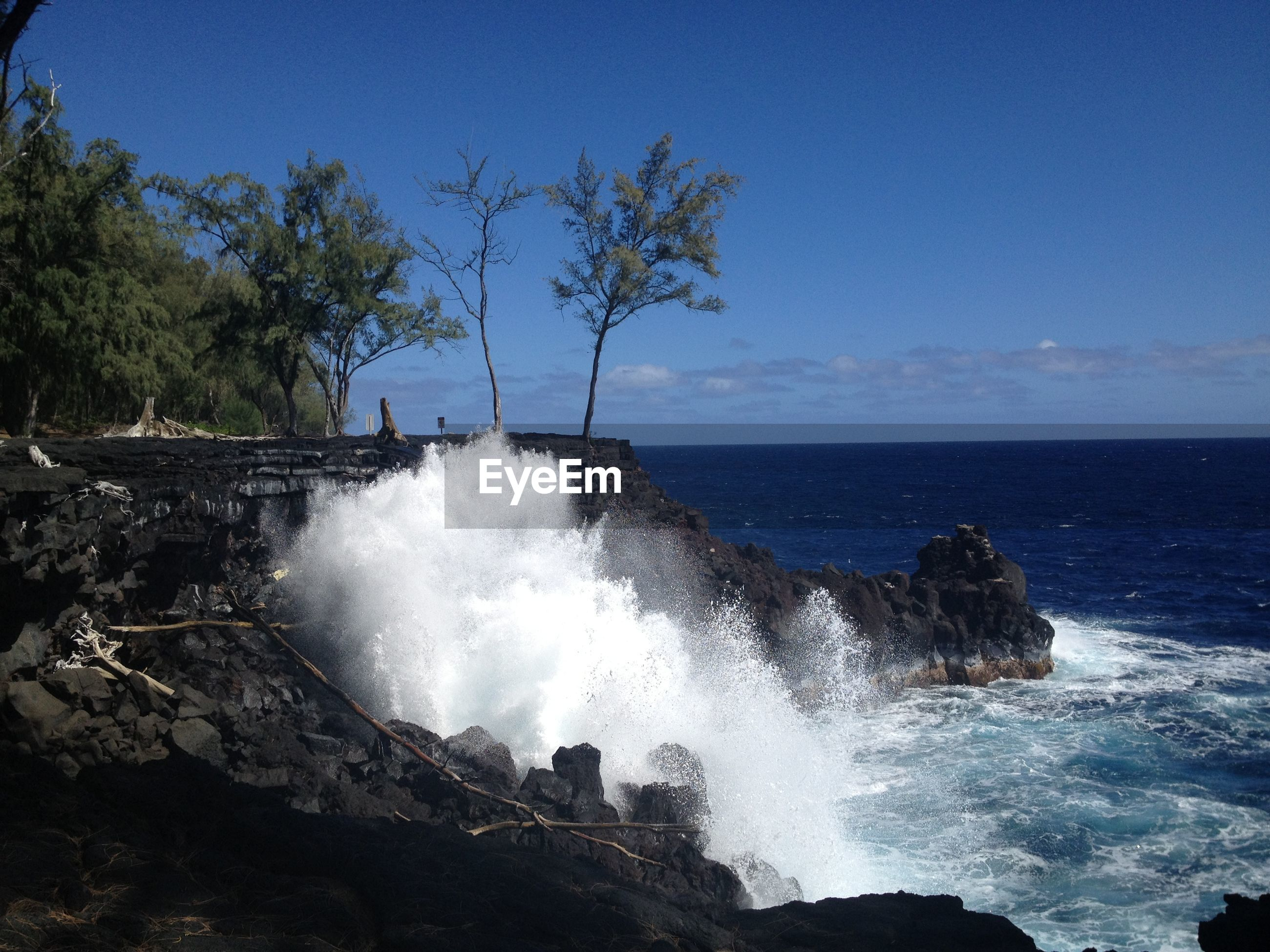 Scenic view of sea splashing on rocks against sky