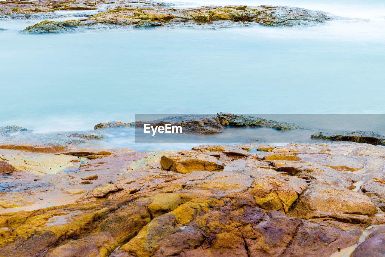 water, rock, solid, beauty in nature, rock - object, nature, tranquility, no people, day, scenics - nature, tranquil scene, outdoors, lake, land, idyllic, motion, beach, high angle view, shallow