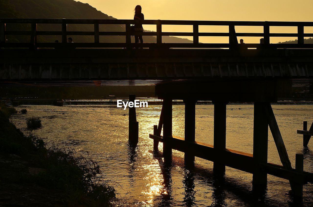Silhouette man on footbridge over river against sky