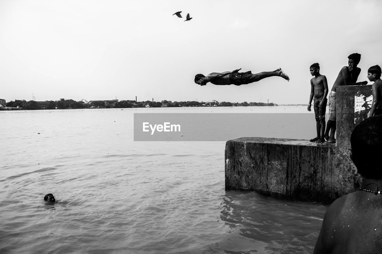 water, real people, sea, mid-air, leisure activity, men, flying, full length, nature, lifestyles, day, outdoors, fun, jumping, sky, motion, beach, standing, vacations, beauty in nature, clear sky, horizon over water, one person, bird, people