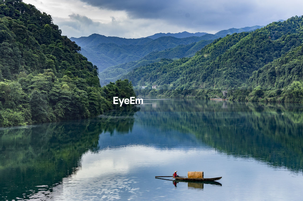 Boat In Lake By Mountains Against Sky